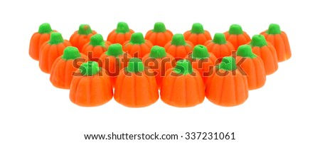 Several rows of orange and green Halloween pumpkin candy isolated on a white background. - stock photo