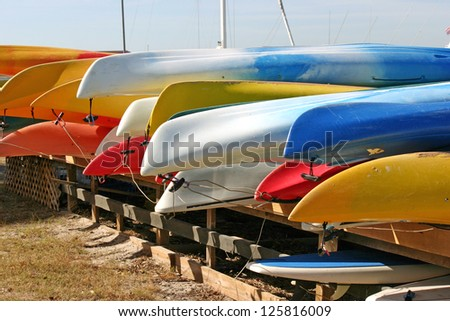 Several rows of pretty, brightly colored canoes - stock photo