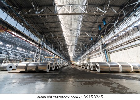 Several rows of rolls of aluminum lie in production shop of plant. - stock photo