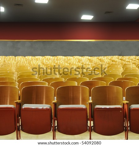 Several rows of theater seats in an auditorium with lights above. - stock photo