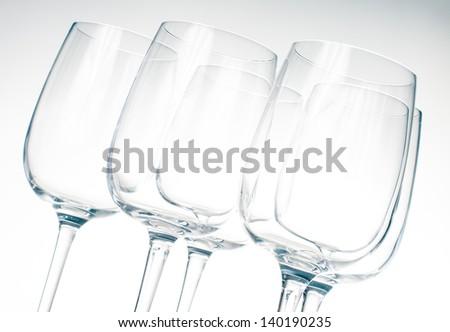 Several same empty  wine glasses in gray shades - stock photo