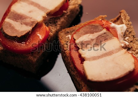 several sandwich with bacon and tomato on dark background.