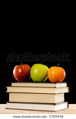 Several school books topped with a variety of apples including a red delicious, a granny smith and a fuji, gifts for teacher, on a black background
