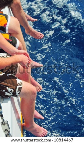 Several sets of men's legs hanging off a catamaran over water - stock photo