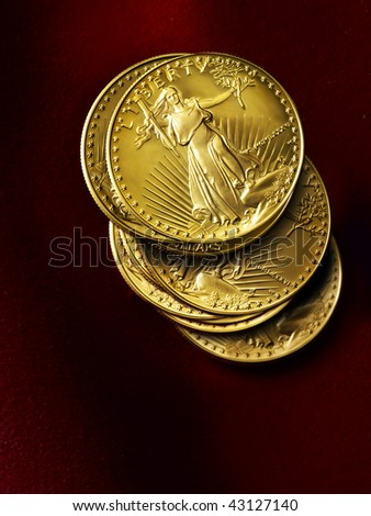 Several shiny gold coins shot on red suede background - stock photo