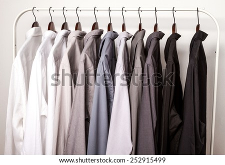 Several shirts on a hanger from white to black color range  - stock photo