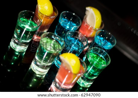 Several shots of different drinks at a party in a nightclub