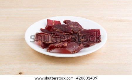 Several slices of hardwood smoked beef jerky on a small white plate atop a wood table top. - stock photo