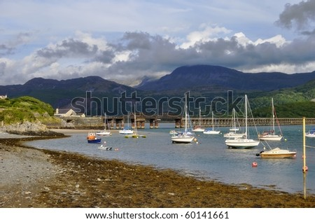 Several small boats, with Barmouth Bridge and the mountain Cadair Idris behind - stock photo
