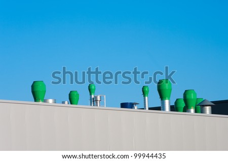 several small chimneys on the roof of an industrial building
