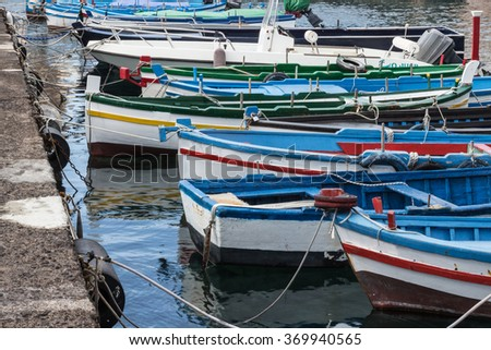 Several small colorful boats are anchored in the harbor of Catania, SIcily-Italy on the coast of the Mediterranean Sea. - stock photo