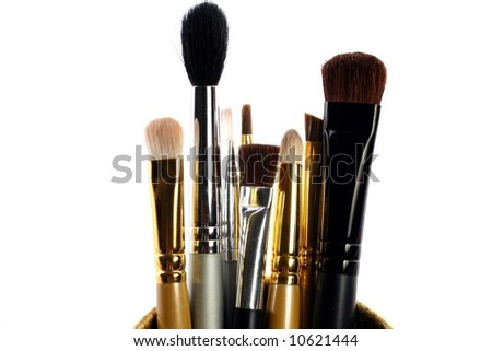several small makeup brushes in a container - stock photo