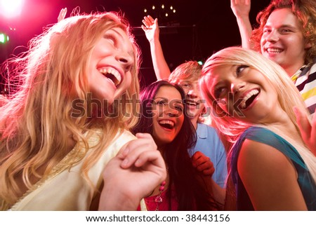 Several smiling dancers having fun during disco