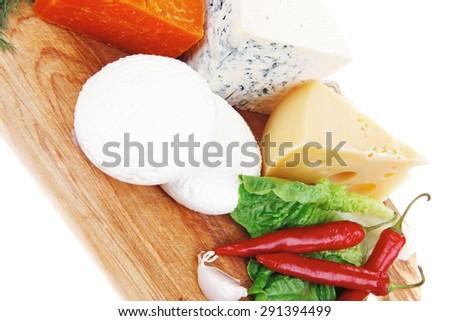 several soft and hard types of french cheese on wooden board with hot peppers and dill isolated on white background - stock photo