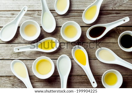 Several soup spoons and sauce dishes arranged randomly on wooden surface - stock photo