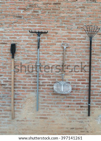 Several Spades and rakes hang and Agricultural Tools with old Brick Wall Background