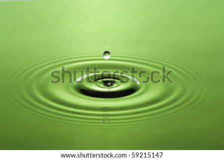 Several splashes on the water and droplets falling down - stock photo
