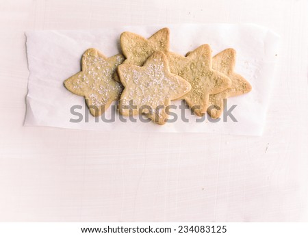 Several star shaped sugar cookies with sprinkles on parchment paper against plain background.  Vintage filter.