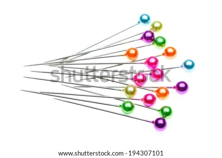 Several straight pins with pastel colored heads stacked on a white surface. - stock photo