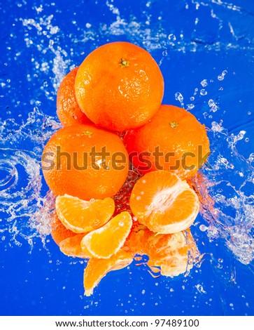 several tangerines in water splash - stock photo