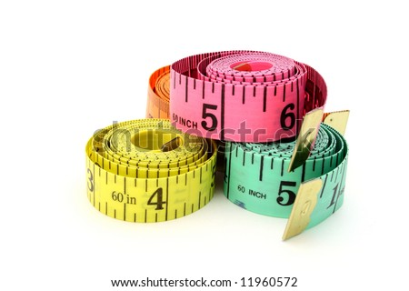 several tape measures over a white surface - stock photo