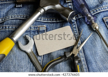 Several tools on a denim workers pocket and business cards on jeans background - stock photo