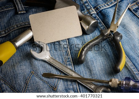 Several tools on a denim workers pocket and business cards on wooden background - stock photo