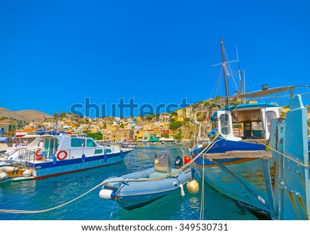 several traditional and touristic boats docked in the main port of Symi island in Greece - stock photo