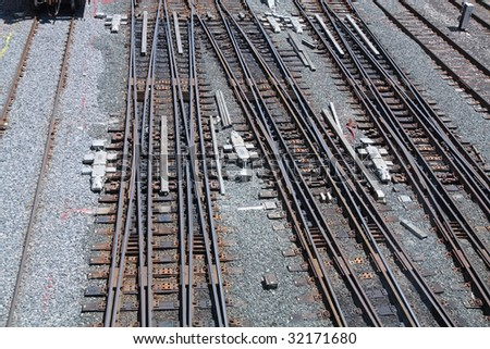 Several train tracks intersect before entering station.