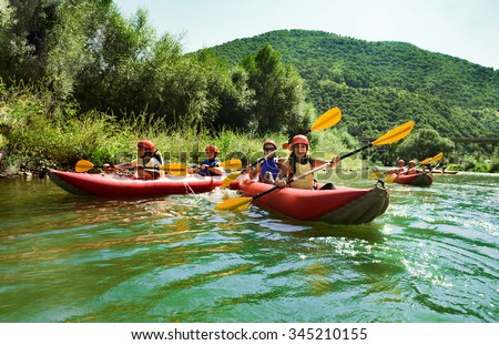 Several two people team inflatable canoes rafting in a calm waters with beautiful surrounding. - stock photo