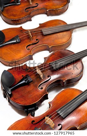 several used fiddles on white background close up