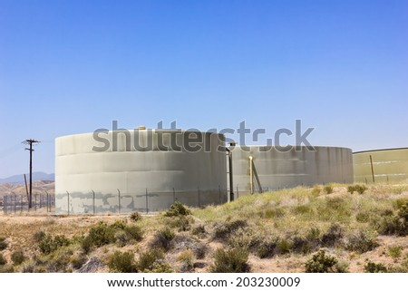 Several water reserve tanks sit up on a hill in a residential community.