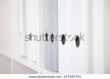 Several White and Gray Binders sitting on shelf. - stock photo