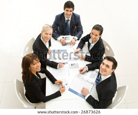 Several white collar workers sitting around table and looking upwards with smiles - stock photo