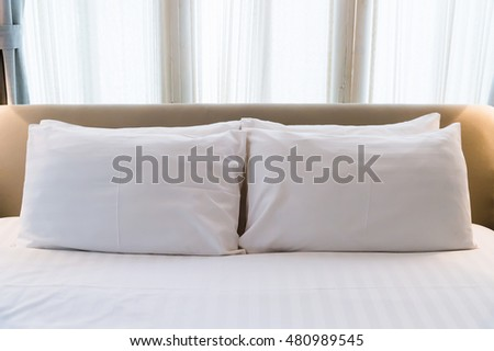 several white pillows on a white bed