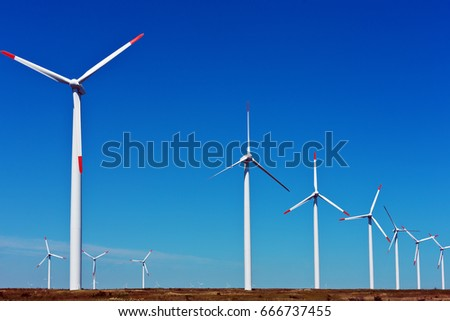 Several wind power turbines standing on a meadow and deep blue sky