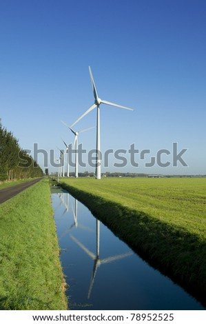 Several wind turbines in a green field and reflection in the water - stock photo