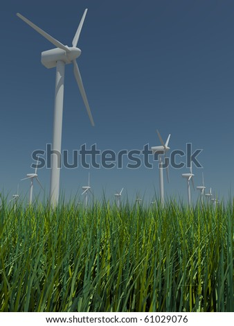 Several windmills standing in the field with grass against the blue sky a bright sunny, windless summer day