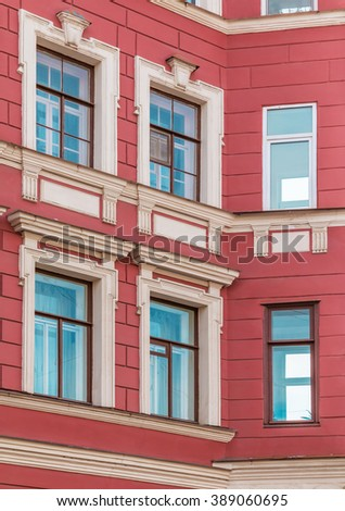 Several windows in row on corner of facade of urban apartment building front view, St. Petersburg, Russia