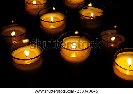 Several yellow candle flame at night closeup in dark church - stock photo