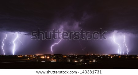 Severe lightning storm over a small city - stock photo