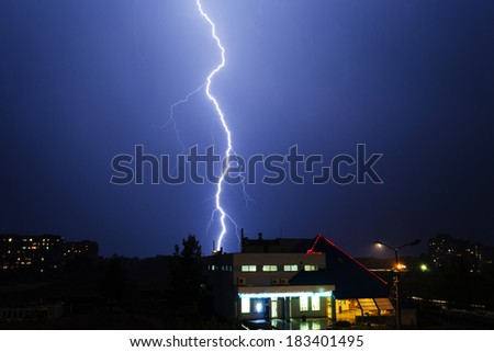 Severe lightning storm with rain over a city buildings at night