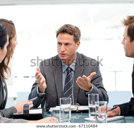 Severe manager talking to his team at a table during a meeting - stock photo