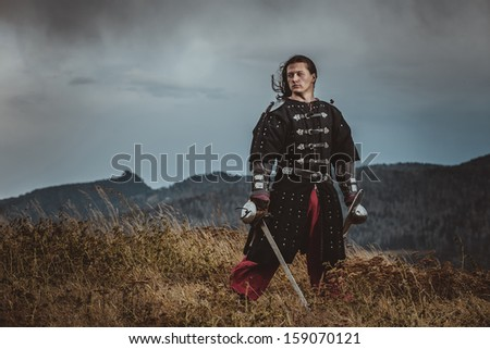 Severe medieval warrior on the shore - stock photo