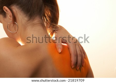Severe Shoulder Pain A young woman holds her back in pain! The area on the shoulder is highlighted to symbolize the pain. - stock photo