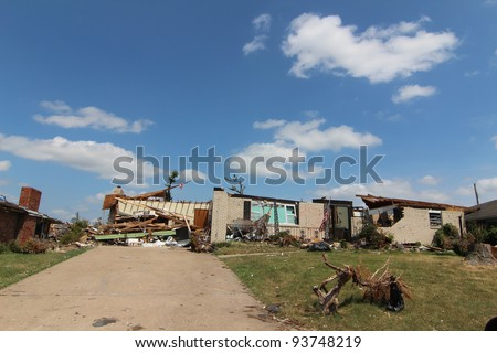 Severe tornado damage to homes and belongings is very apparent in the light of a beautiful blue sky sunny day. - stock photo