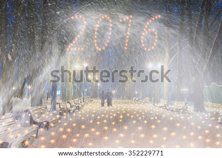 Severe weather in Kiev citizens favorite park, twilight hid fog and snowfall old trees, fall asleep benches, lights shine through the mist cold and damp, a strong wind blows snowflakes quickly through - stock photo