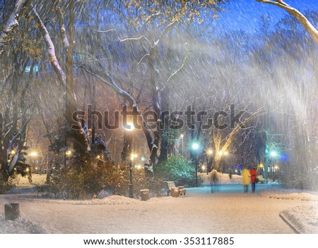 Severe weather in Kiev citizens favorite park, twilight hid fog and snowfall old trees, fall asleep benches, lights shine through the mist,  a strong wind blows snowflakes quickly through the branches - stock photo