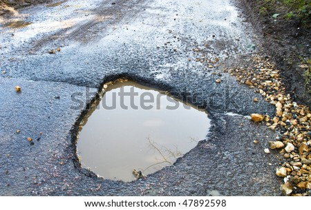 Severe winter damage to a tarmac road producing a large, deep ,waterfilled pothole - stock photo