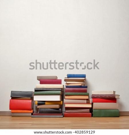 Severel stacks of old books on wooden floor - stock photo